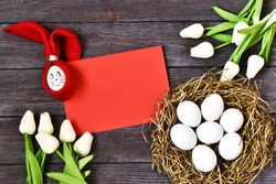 Happy easter. Napkin Easter Bunny and nest eggs with bouquet of tulips,red paper and inscription wood letters HAPPY EASTER on a wooden table. Copy space, flat lay.