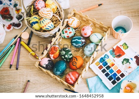 Happy Easter! Painting eggs. Paints, felt-tip pens, decorations for coloring eggs for holiday. Creative background. Family with kids preparing for Easter.
