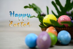 Happy Easter text and decoration with white background of colorful easteregg on wooden rattan basket and green leaves. Easter eggs on Easter Day concept.
