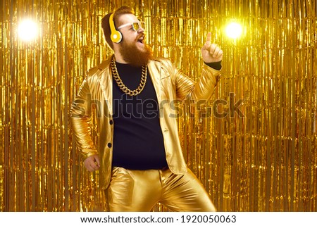 Happy eccentric redhead man wearing crazy suit, gold neck chain and stylish wireless headphones enjoying free unlimited online music, listening to favorite audio track, singing, dancing and having fun Foto stock ©