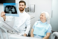 Happy elder woman during the consultation with handsome dentist showing panoramic x-ray in the dental office