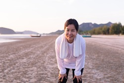 Happy elderly asian woman break and relax after workout at the beach in the morning