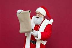 Happy elderly bearded Santa Claus wearing costume, hat, glasses, holding parchment roll reading letter wish list preparing for xmas eve isolated on red background. Merry Christmas wishlist ad concept.