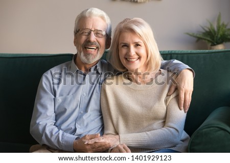 Happy elderly blond wife hoary husband in glasses having sincere feelings candid toothy smile, spouses hugging resting on couch at home, dental care services medical insurance for older people concept
