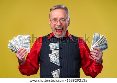 Happy elderly business man with fan of dollar bills. Isolated on yellow background. Senior man guy won the lottery. Lucky day. Human emotions and facial expressions Stock photo ©