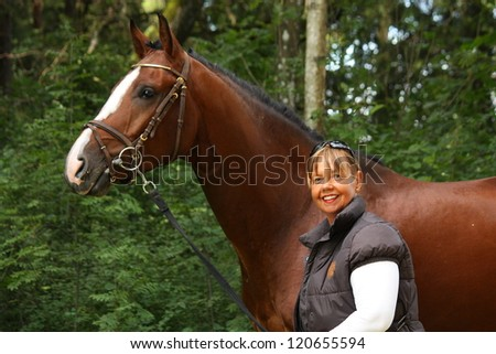 Happy elderly caucasian woman and bay latvian horse portrait in forest - stock photo