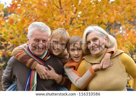 happy elderly couple and grandchildren together resting