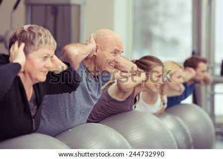 Happy elderly couple exercising in a pilates class at the gym with three other younger people toning and strengthening their muscles using gym balls, focus to the senior man and woman