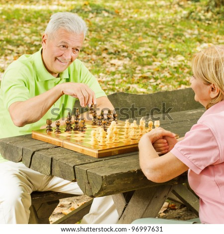 Happy elderly couple has fun playing chess in the park.