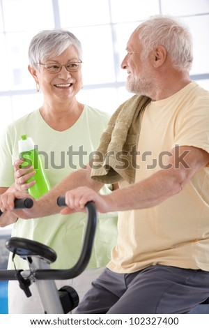 Happy elderly couple in the gym, man on fitness cycle.