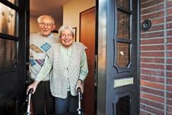 Happy Elderly Couple Opening the Front Door