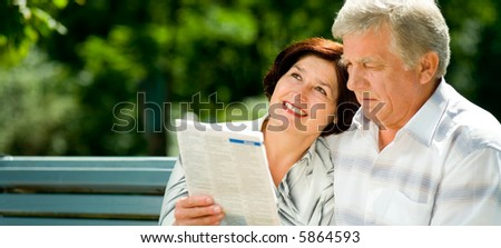 Happy elderly couple reading together outdoors. Focus on woman. To provide maximum quality I have made this image by combination of two photos. - stock photo