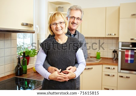 Happy elderly couple standing smiling in a new kitchen