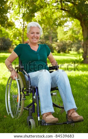Happy elderly disabled woman in a wheelchair in a park