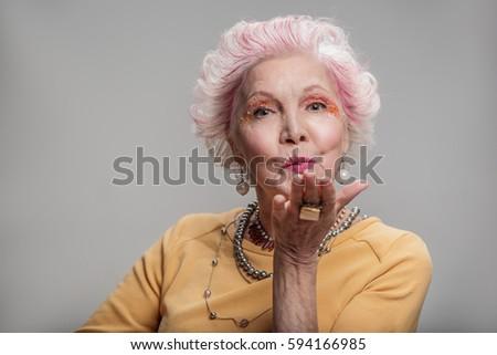 Happy elderly female posing with bright make-up