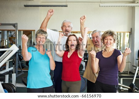 Happy elderly group in a gym cheering