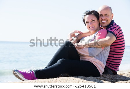Happy elderly man and a woman happily embracing each other on the beach