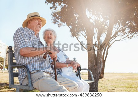 Happy elderly man and woman sitting on a bench with walking stick on a summer day. Relaxed senior couple sitting on a park bench.