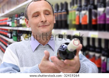 happy elderly man in shop looks on  wine bottle in hands