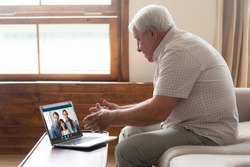 Happy elderly mature 80s man holding video call with family grown up children and granddaughter, communicating online via laptop videoconference application, staying at home isolation, virus outbreak.