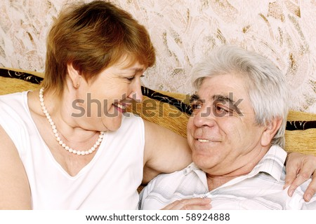 Happy elderly pair contact with each other
