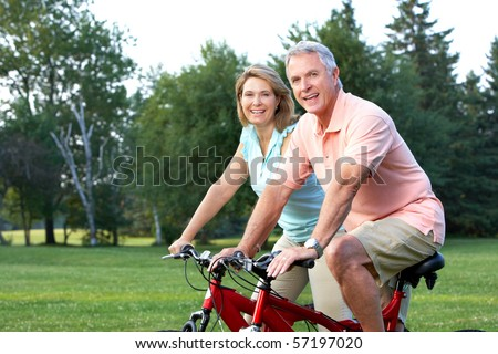 Happy elderly senior couple biking in park - stock photo