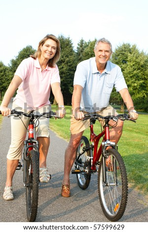 Happy elderly senior couple cycling in park