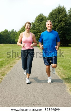 Happy elderly senior couple jogging in park