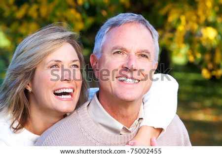 Happy elderly seniors couple in park. Love. - stock photo