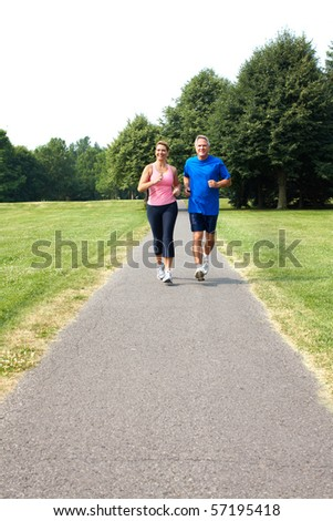 Happy elderly seniors couple jogging in park