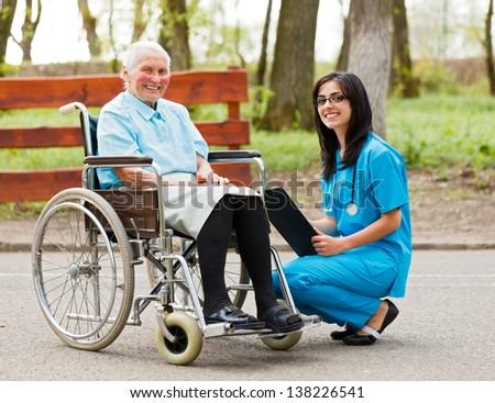Happy elderly woman in wheelchair and kind nurse outdoors.