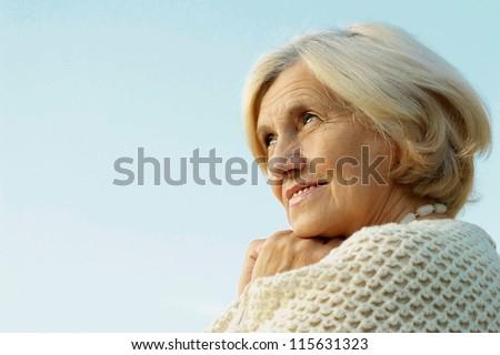 Happy elderly woman posing against the sky