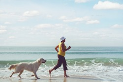 Happy elderly woman running along a beach with her golden retriever at the morning