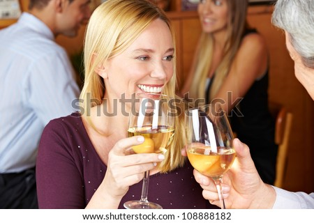 Happy elderly woman toasting with glass of white wine to man