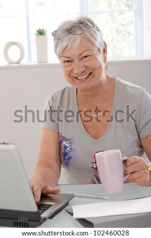 Happy elderly woman using laptop computer, smiling, drinking tea.