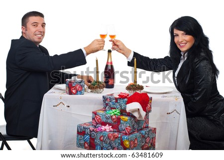 Happy elegant couple toast with champagne at Christmas dinner and looking you