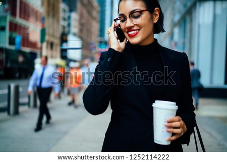 Happy elegant female entrepreneur talking on cellphone about business while passing crosswalk in megalopolis, successful lawyer holding coffee to go during phone conversation on urban setting #1252114222