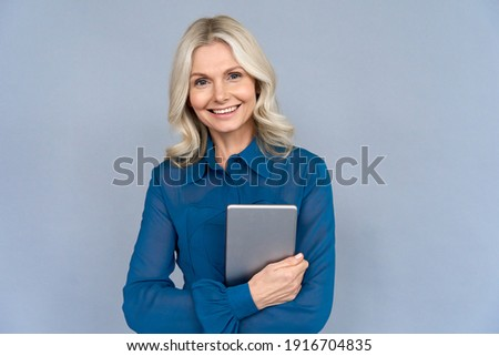 Happy elegant middle aged older professional business woman leader, consultant manager, looking at camera holding digital tablet isolated on grey wall advertising corporate online e learning webinars.