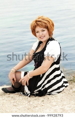 happy elegant middle aged plus size woman resting near sea shore and smiling with beautiful makeup and healthy glossy hair. Rich lady relaxing at beach spring-summer