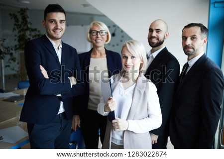 Happy elegant professionals standing in conference hall at break between events and looking at you #1283022874