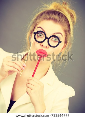 Happy elegant woman holding carnival accessoies on stick having fun at work wearing white office jacket #733564999