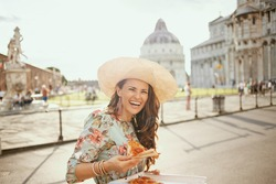 happy elegant woman in floral dress with pizza and hat in piazza dei miracoli in Pisa, Italy.