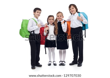 Happy elementary school kids with colorful back packs - isolated