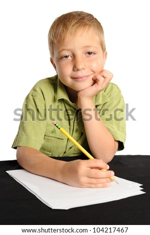 Happy Elementary School Student. Young boy smiling as he starts to work on his schoolwork.