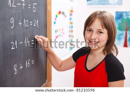 Happy elementary schoolgirl writing equation solution on chalkboard