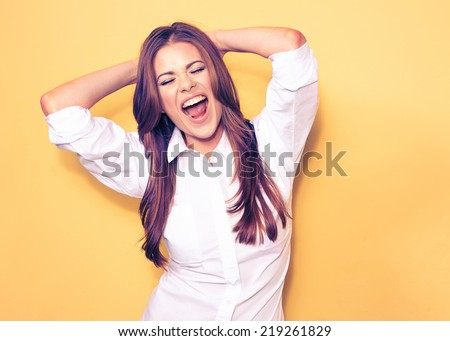 happy emotional business woman portrait . smiling model, white shirt. yellow background.