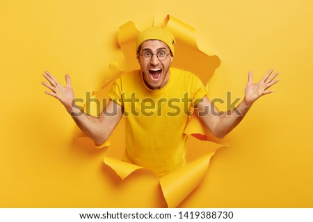 Happy emotional Caucasian man shows huge gesture, measures something big, shouts loudly, wears yellow headgear and t shirt, poses in torn paper wall. People and size concept. Monochrome shot