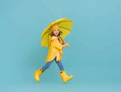 Happy emotional child laughing and jumping. Kid with yellow umbrella on colored teal background.