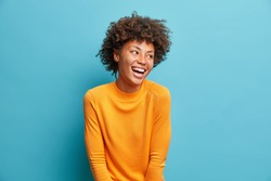 Happy emotions concept. Positive dark skinned beautiful young woman laughs poisitively looks aside with carefree face expression wears casual orange sweater isolated over blue studio background.