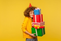 Happy emotions from big mountain of gifts. Portrait of pleased happy curly-haired woman with party cone embracing many present boxes, celebrating birthday. studio shot isolated on yellow background